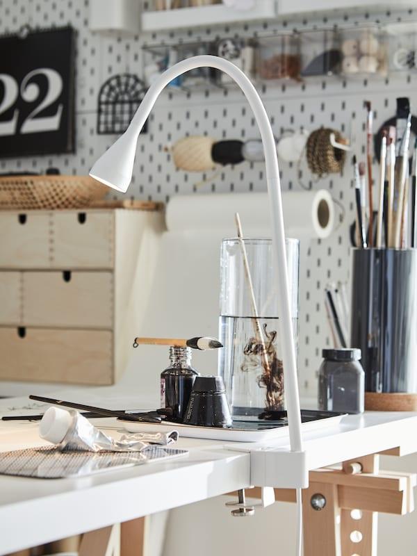 Työpöytä, jonka kulmaan on kiinnitetty valkoinen NÄVLINGE-työvalaisin. Pöydällä on maalaustarvikkeita ja MOPPE-minilipasto. Seinään on kiinnitetty SKÅDIS-taulu jossa roikkuu myös MÅLA-piirustuspaperirulla.