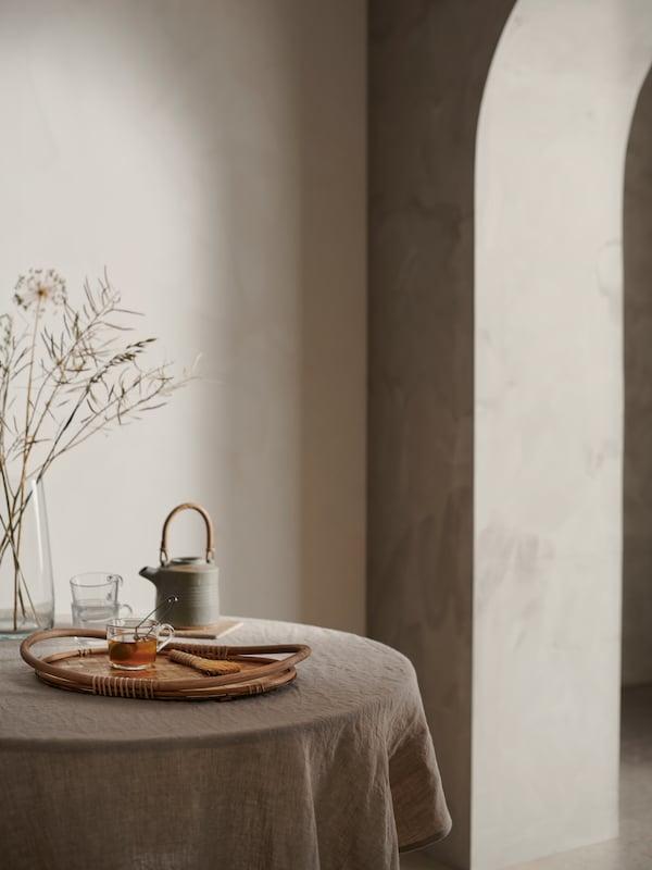 Tava VÅRFINT așezată pe o măsuță rotundă într-un cadru liniștit, împreună cu un ceainic din ceramică și căni de sticlă.