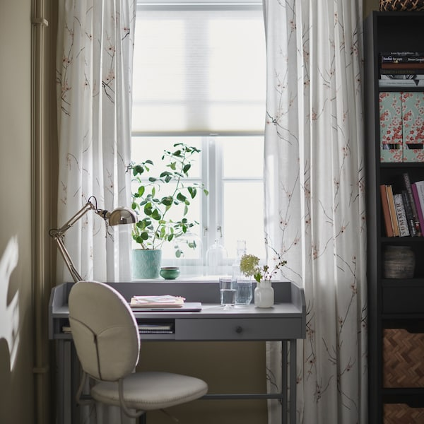 A work desk in front of a window, framed in with white curtains with a cherry blossom pattern and a green plant on the window sill.