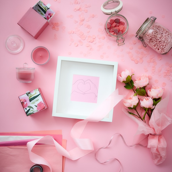 A pink background with a white frame surrounded by other pink accents