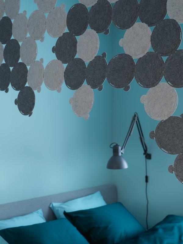 Un ciel de lit fait de panneaux acoustiques ODDLAUG est suspendu au-dessus de la tête d'un lit. Une lampe de travail TERTIAL est fixée au mur.