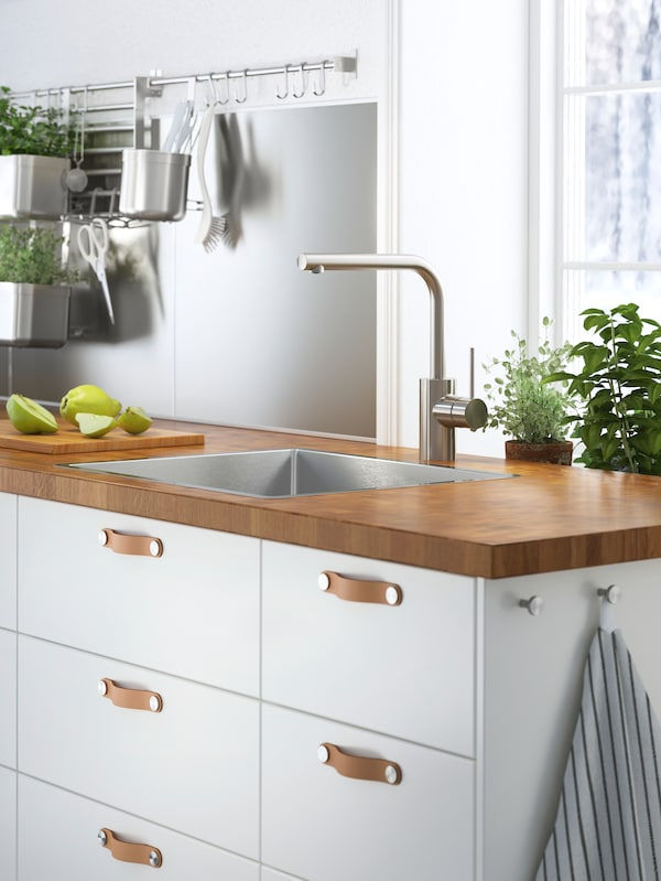 A worktop in thick oak veneer on a cabinet with white fronts and leather handles. A sink and a cutting board with pears.