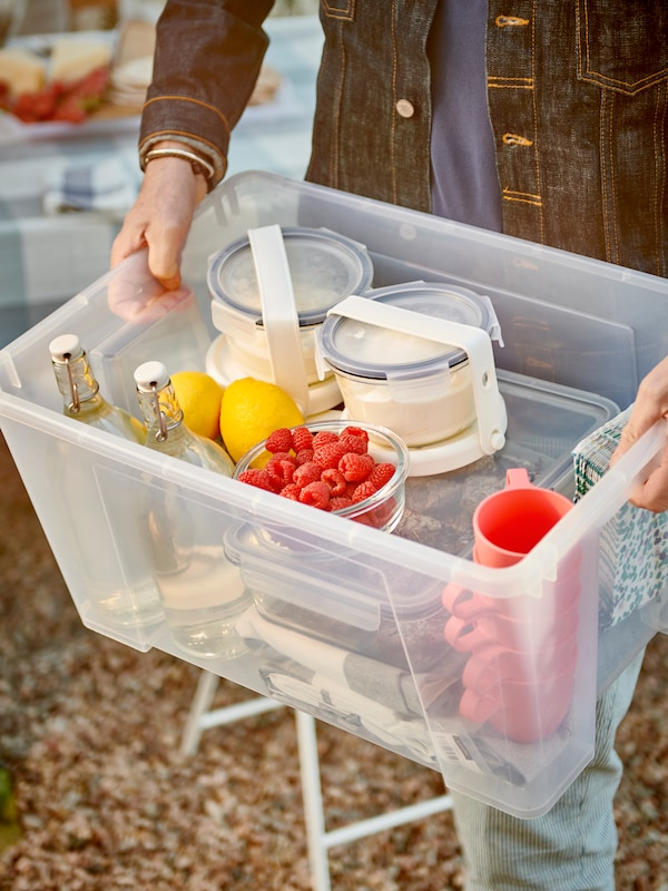 Hands holding a SAMLA box filled with tableware, glass bottles and food containers strapped to IKEA 365+ ice packs.