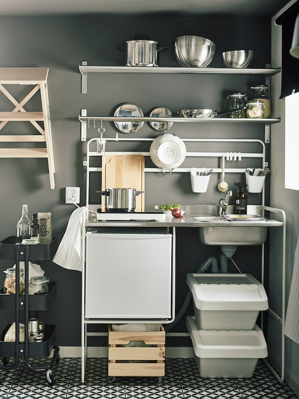 A white SUNNERSTA mini-kitchen against a dark grey wall, with white shelves on top holding pots and pans in stainless steel.