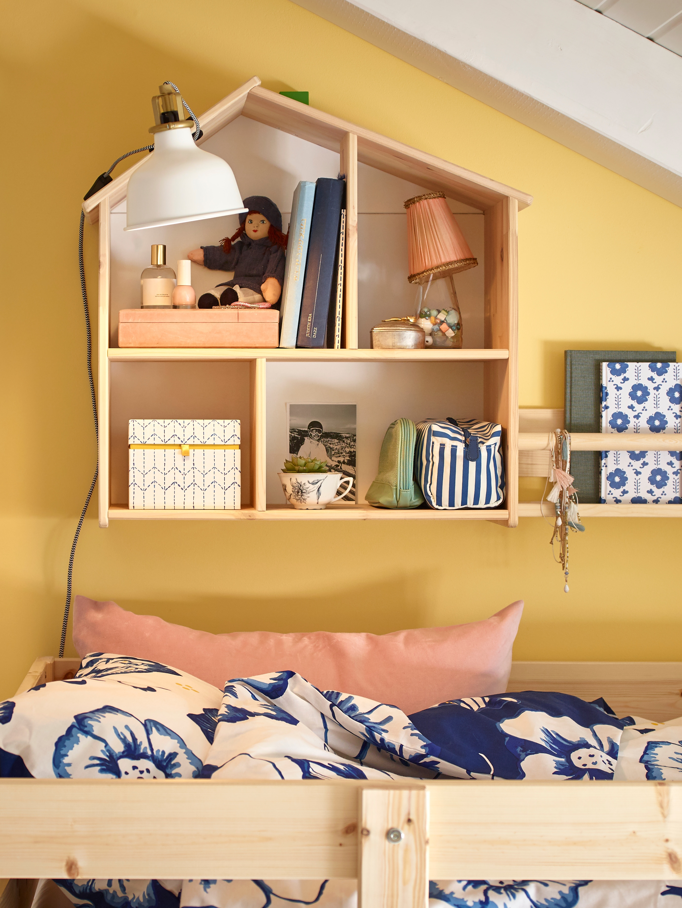 A pine FLISAT doll's house/wall shelf holds various toys and children's items on a wall, above a bunk bed with bed linen.