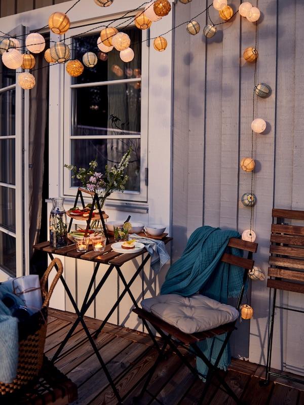 Ett set med TÄRNÖ stolar och bord mot en husvägg, uppdukat med middag för en.