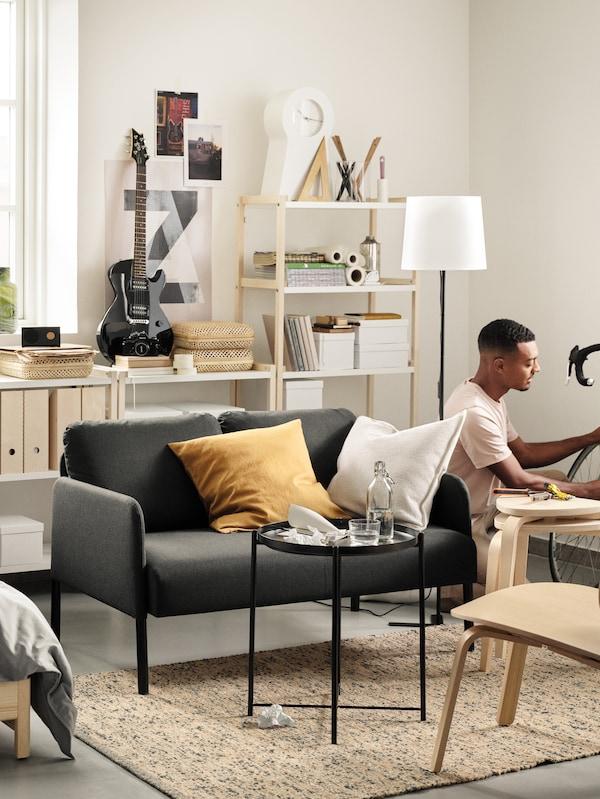 Sala de estar iluminada cun sofá GLOSTAD pequeno detrás dunha mesa bandexa negra xunto a un home de xeonllos fronte a unha bicicleta.