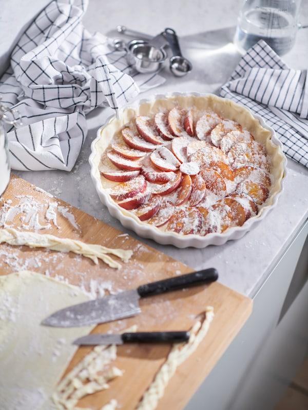 Eine Arbeitsplatte mit FÖRDUBBLA Messern und Teigstücken auf einem LÄMPLIG Schneidebrett. Daneben ist ein ungebackener Pfirsichkuchen in einer VARDAGEN Form zu sehen.