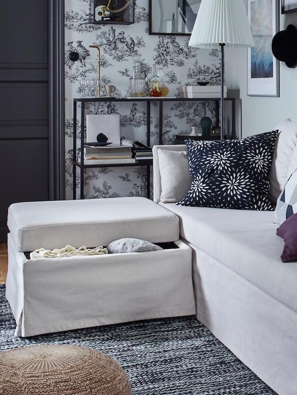 IKEA SANDBACKEN Sofa mit einem Hocker, dessen Polster leicht zur Seite geschoben ist und den Blick auf Bettwäsche freigibt.