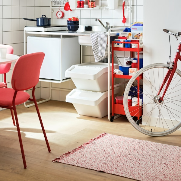 A RÖRKÄR flatwoven rug lies on the floor near a red KARLJAN chair, two SORTERA waste sorting bins with lids and a bicycle.