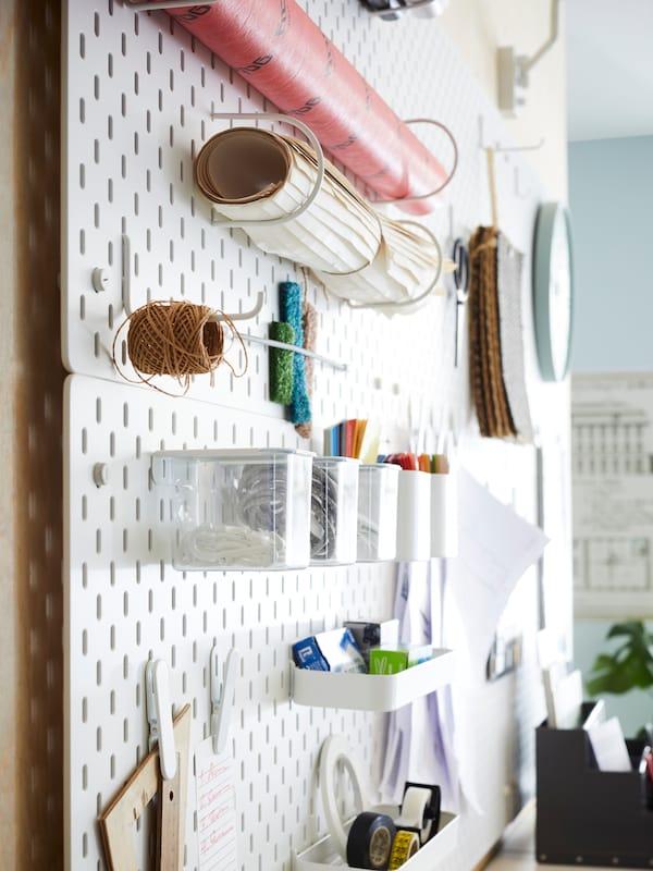 Pannelli portaoggetti bianchi SKÅDIS con appesi vari materiali e articoli di cancelleria in una zona comune dell'ufficio.