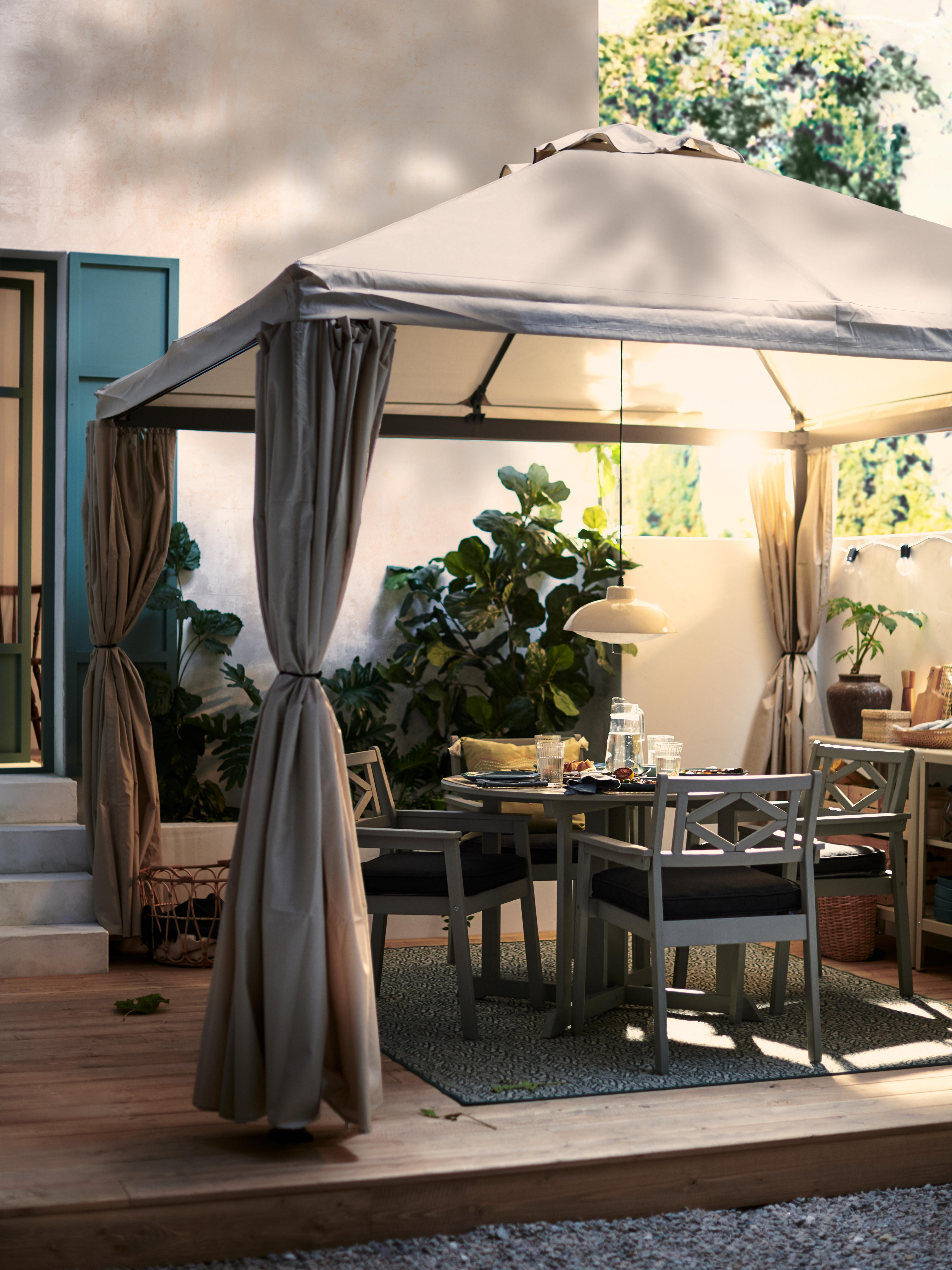 Sivi BONDHOLMEN baštenski trpezarijski sto i stolice, za četiri osobe i uživanje u večeri u dvorištu ispod senice.