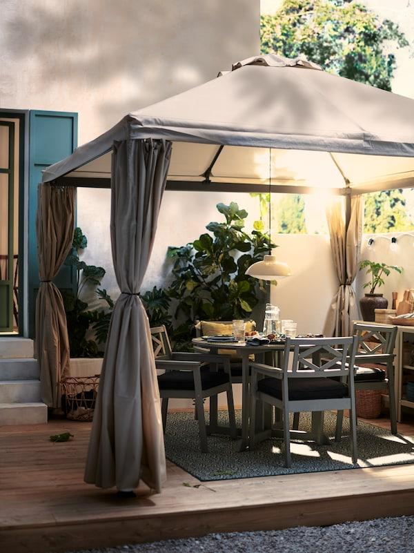 Mesa de comedor ao aire libre BONDHOLMEN gris e cadeiras para catro persoas preparadas para unha cea ao aire libre nunha terraza baixo unha pérgola de tea.
