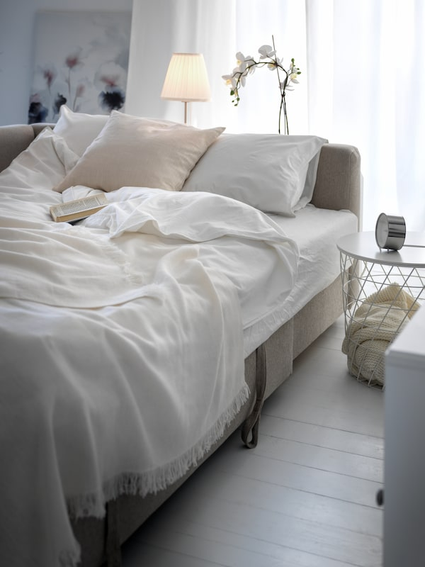A beige FRIHETEN sofa-bed made as a bed with white ÄNGSLILJA bed linen and with a bedside KVISTBRO storage table.