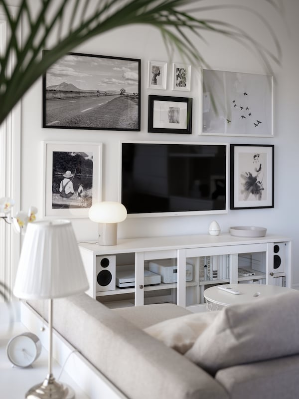 A wall-mounted TV hangs amid framed art over a white HAVSTA TV bench opposite a beige FRIHETEN sofa-bed in a living room.