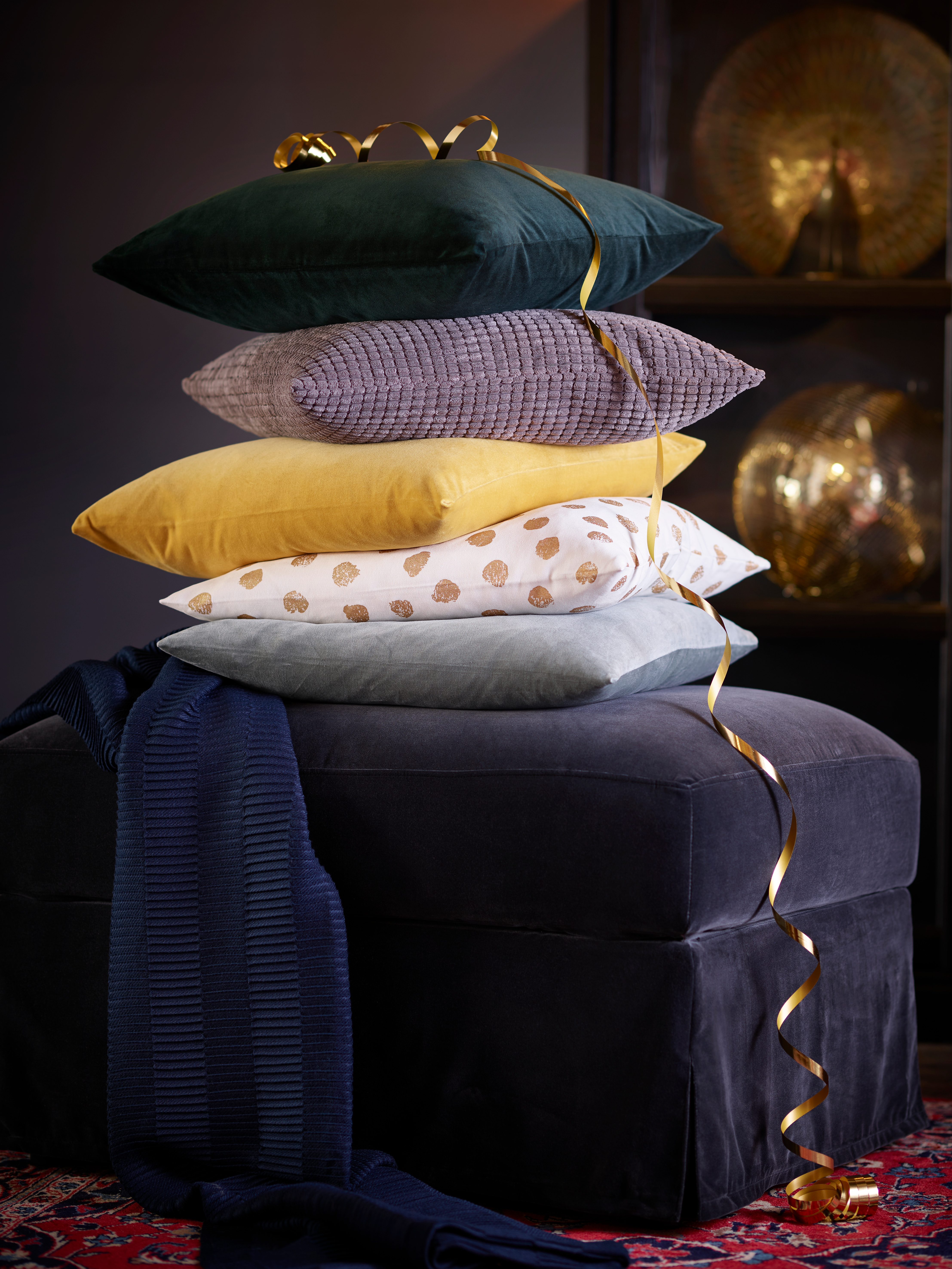 A footstool holds many stacked cushions, including a dark green SANELA cushion cover. A gold ribbon is draped on everything.