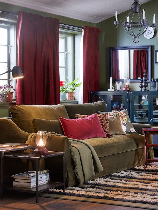 A living room with red-brown SANELA curtains on two windows behind a green sofa with cushions and an ODDRUN throw on it.