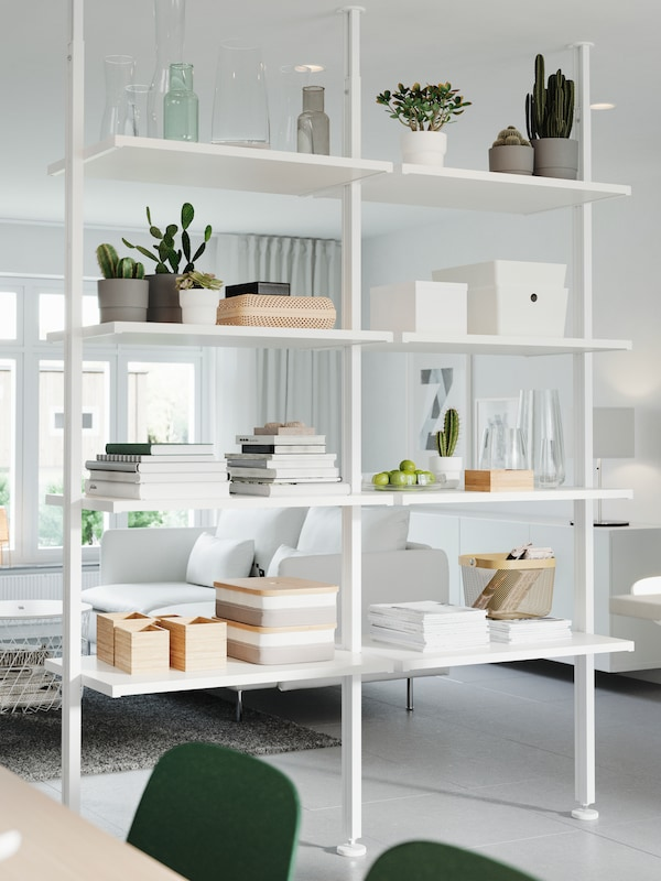 A white storage system that's used as a room divider. Decorative items, plants, books and storage boxes stand on the shelves.