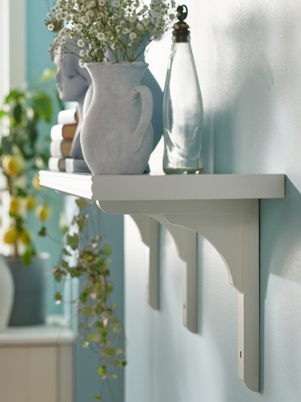 A bottle, a vase with flowers and other items sit on a white BERGSHULT shelf attached to the wall by RAMSHULT brackets.