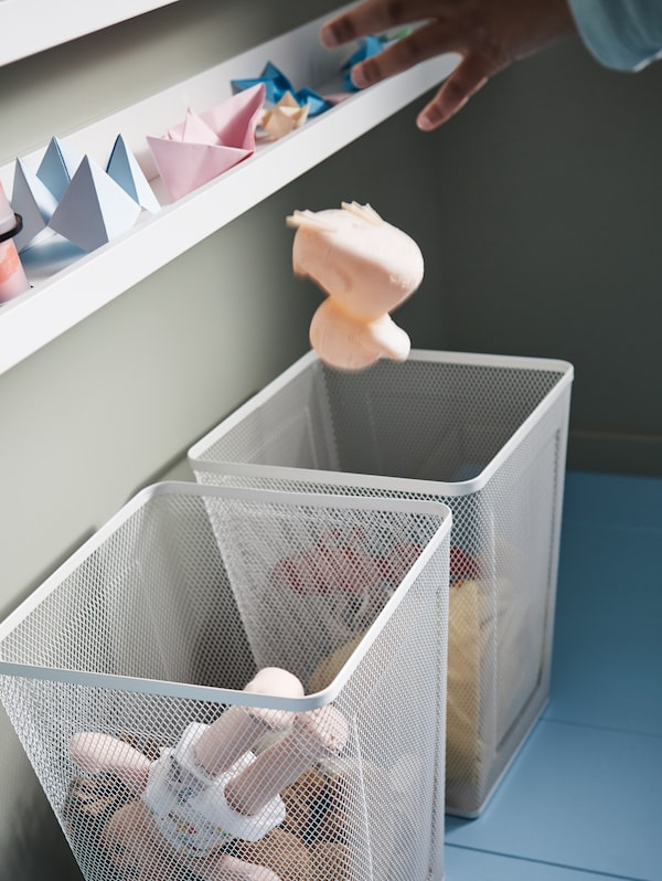 A picture ledge, two white DRÖNJÖNS wastepaper baskets with toys inside and a boy's hand throwing a toy into one of them.