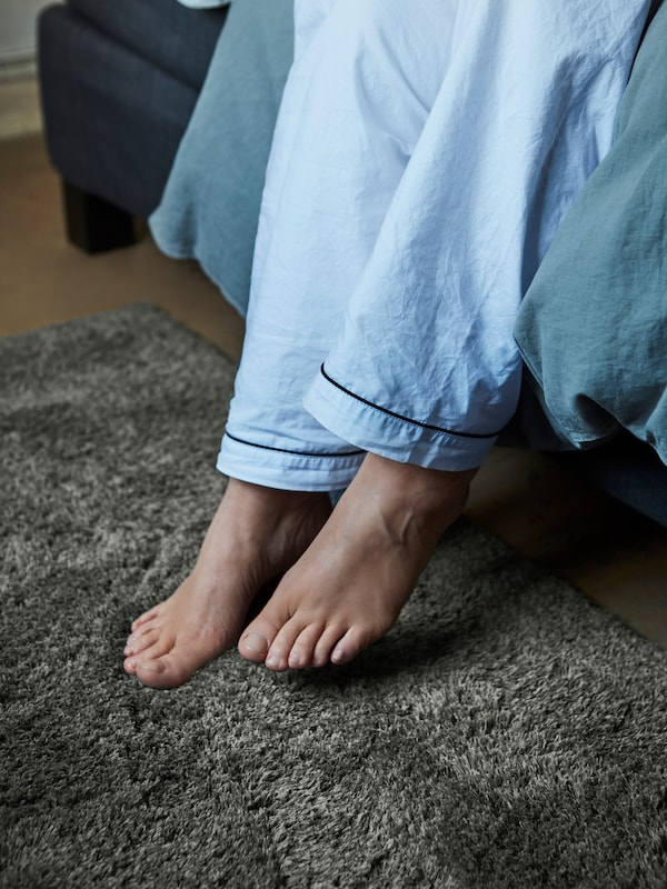 A woman's feet stepping out of bed onto a dark grey LINDKNUD rug. She is wearing light blue pyjama pants.