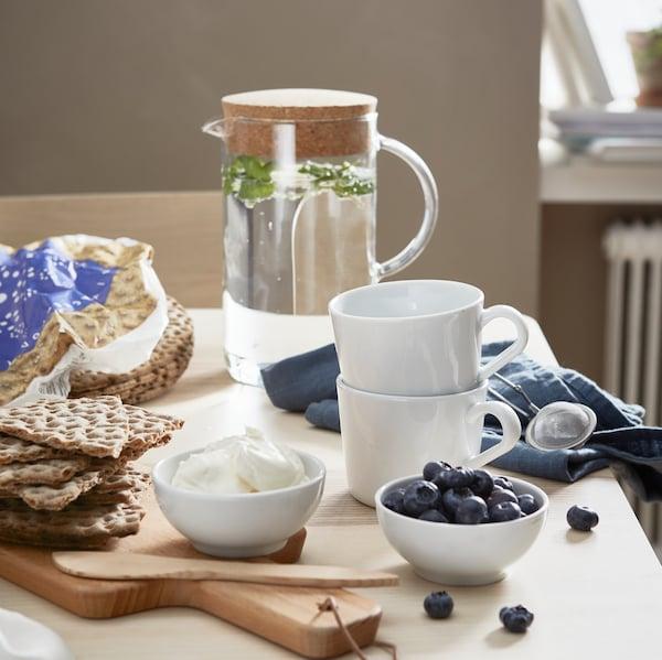 Une table de cuisine avec du pain croustillant sur une planche à découper, deux bols contenant des myrtilles et du fromage à la crème et deux tasses blanches.