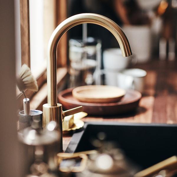 صورة عن قرب لحنفية المطبخ DELSJÖN فوق حوض مع أطباق وأكواب في الخلفية.