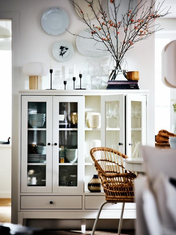 Dans une pièce blanche de style campagnard, une vitrine IDANÄS blanche pleine d'objets, à côté d'un fauteuil NILSOVE.