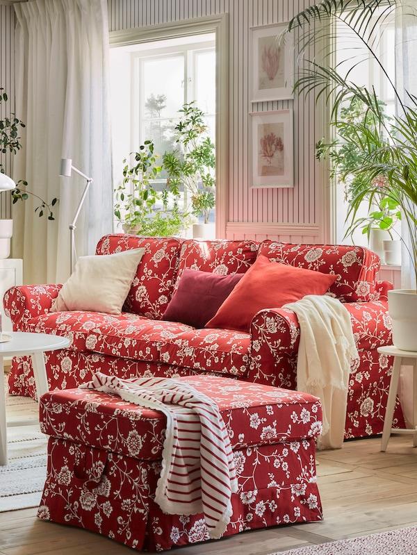 Een bank met rood en wit patroon met kussens in verschillende kleuren, een bijpassende voetenbank, planten en ramen op de achtergrond.