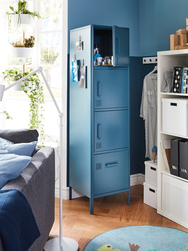 A blue storage cabinet with the top compartment door open, white shelving with diverse items and the back of a sofa.