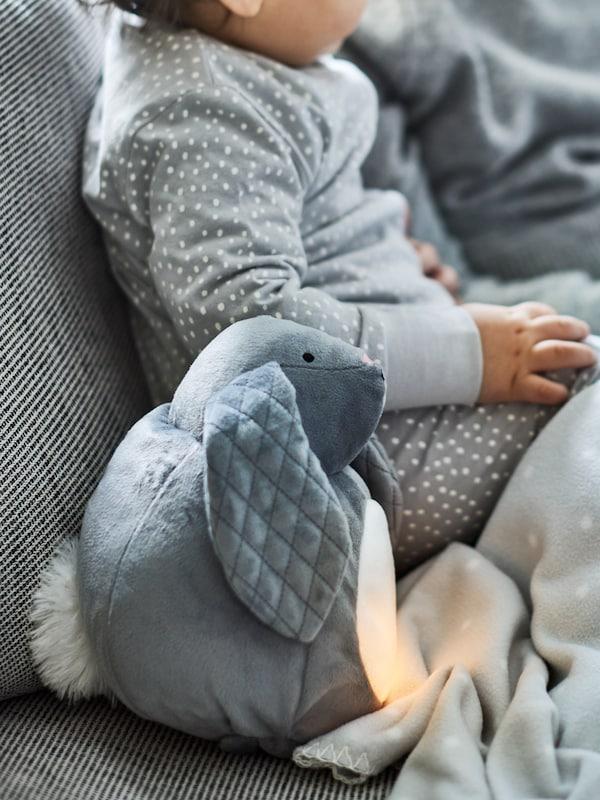 Malé dítě v tečkovaném pyžamu sedí na pohovce vedle plyšové hračky PEKHULT s LED nočním světlem, jehož světlo svítí.