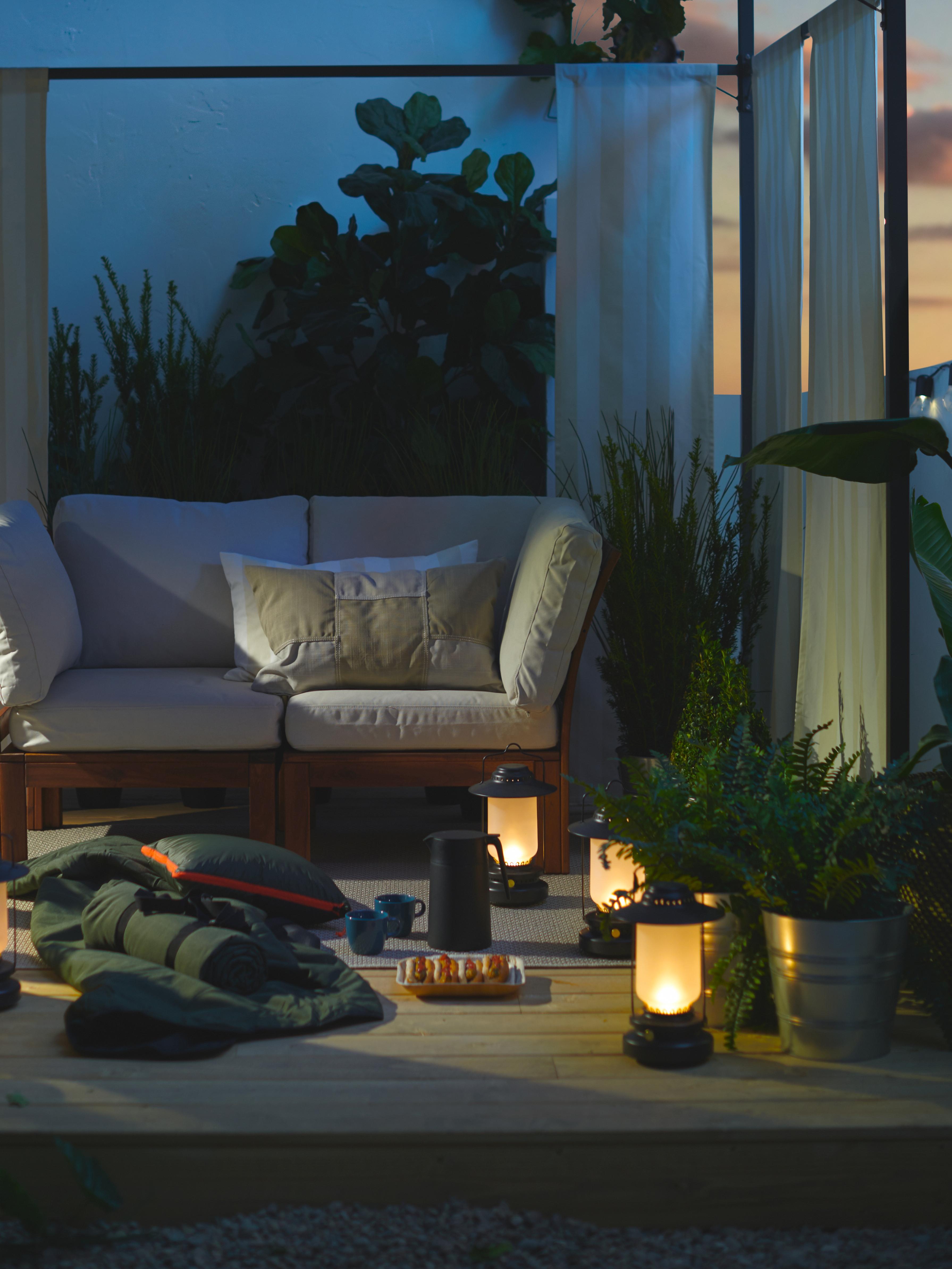 Un décor rappelant une aire de camping avec des lanternes à LED, une couverture, des hot dogs et des boissons chaudes sur une terrasse sous une tonnelle au crépuscule.
