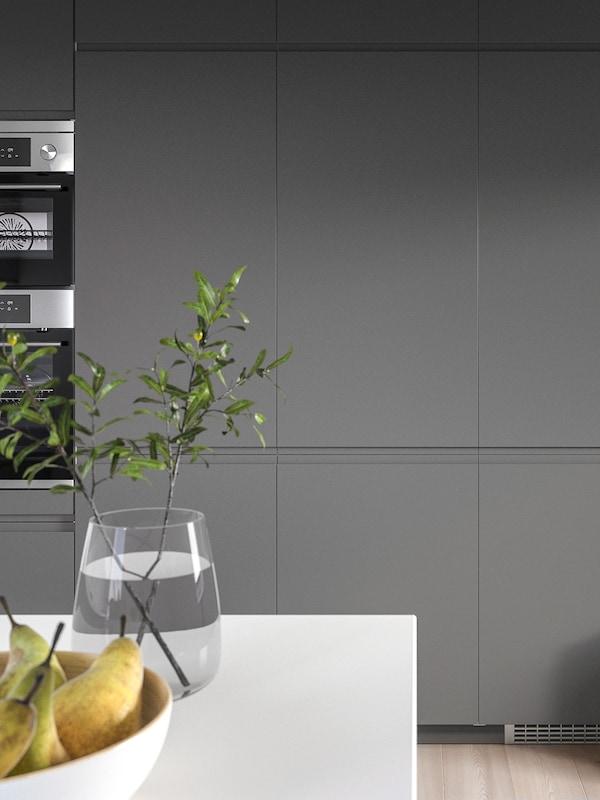 Frentes de cocina grises con electrodomésticos de acero inoxidable, una mesa con un cuenco con peras y un vaso con dos ramitas.