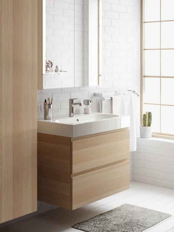 Un meuble de salle de bain en bois blanc avec un lavabo blanc sous une armoire de toilette combiné avec un placard suspendu sur une fenêtre avec cactus