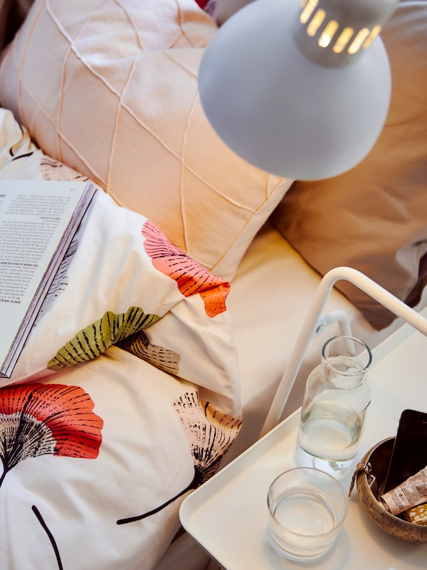 A TERTIAL work lamp shines on a NESTTUN bed with a floral quilt, pillows and a book, and on a small white side table.