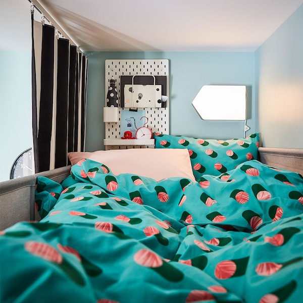 A kid's room with a bed with GRACIÖS bed linen and a SKÅDIS pegboard and a BÄGAREN LED wall lamp on the wall.