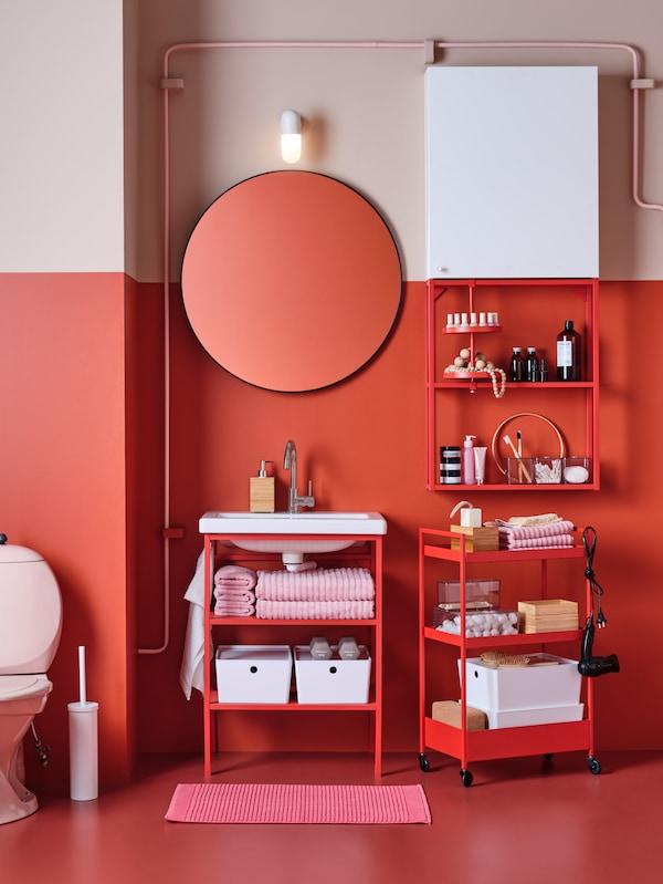 O baie cu mobilier de baie roșu-portocaliu, cum ar fi un corp de perete, o mască de lavoar deschisă și o oglindă rotundă.