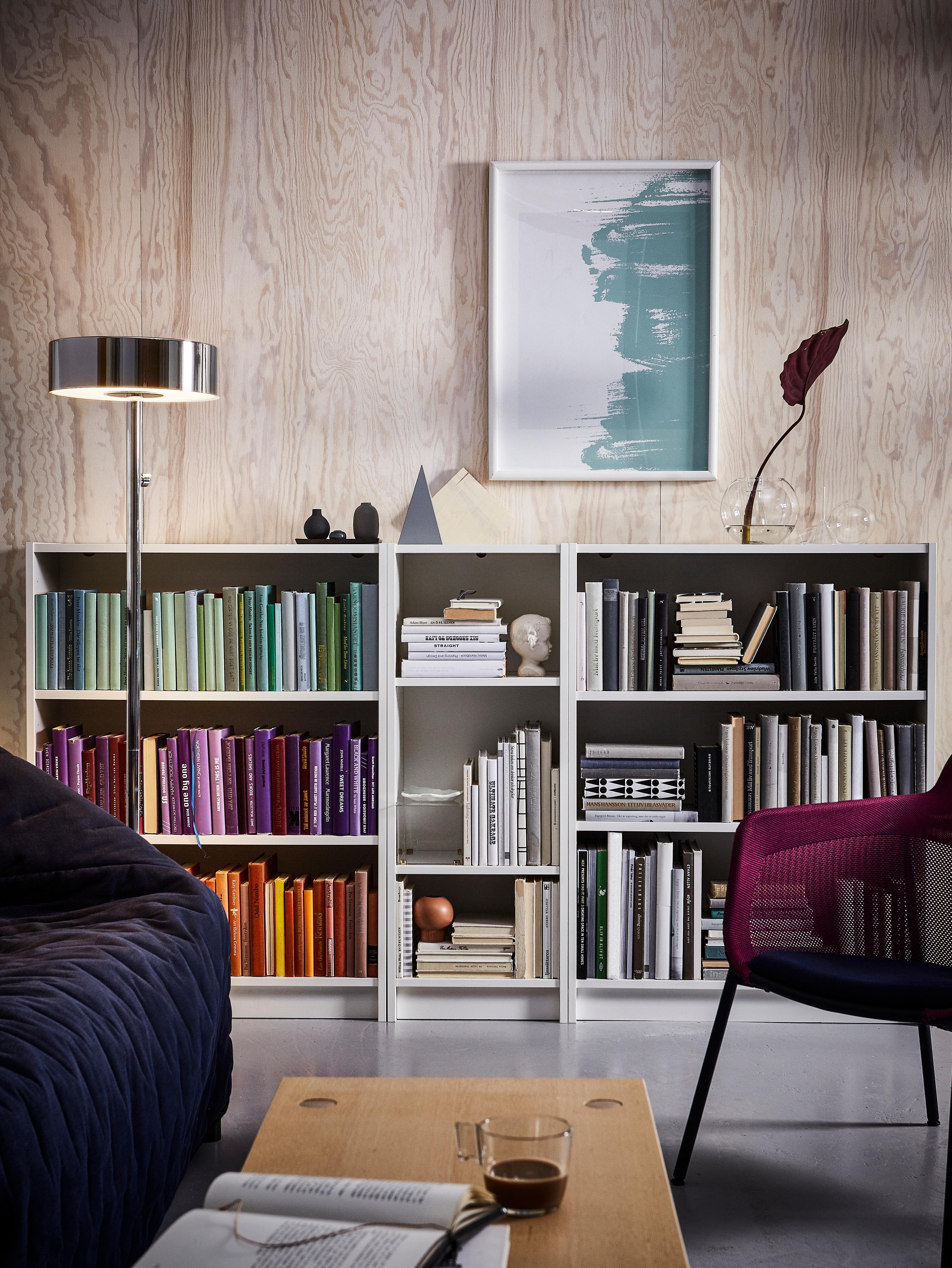 Tres estantes BILLY nun salón rosa cheo de libros de cores. Un sofá azul mariño e unha cadeira morada están diante.