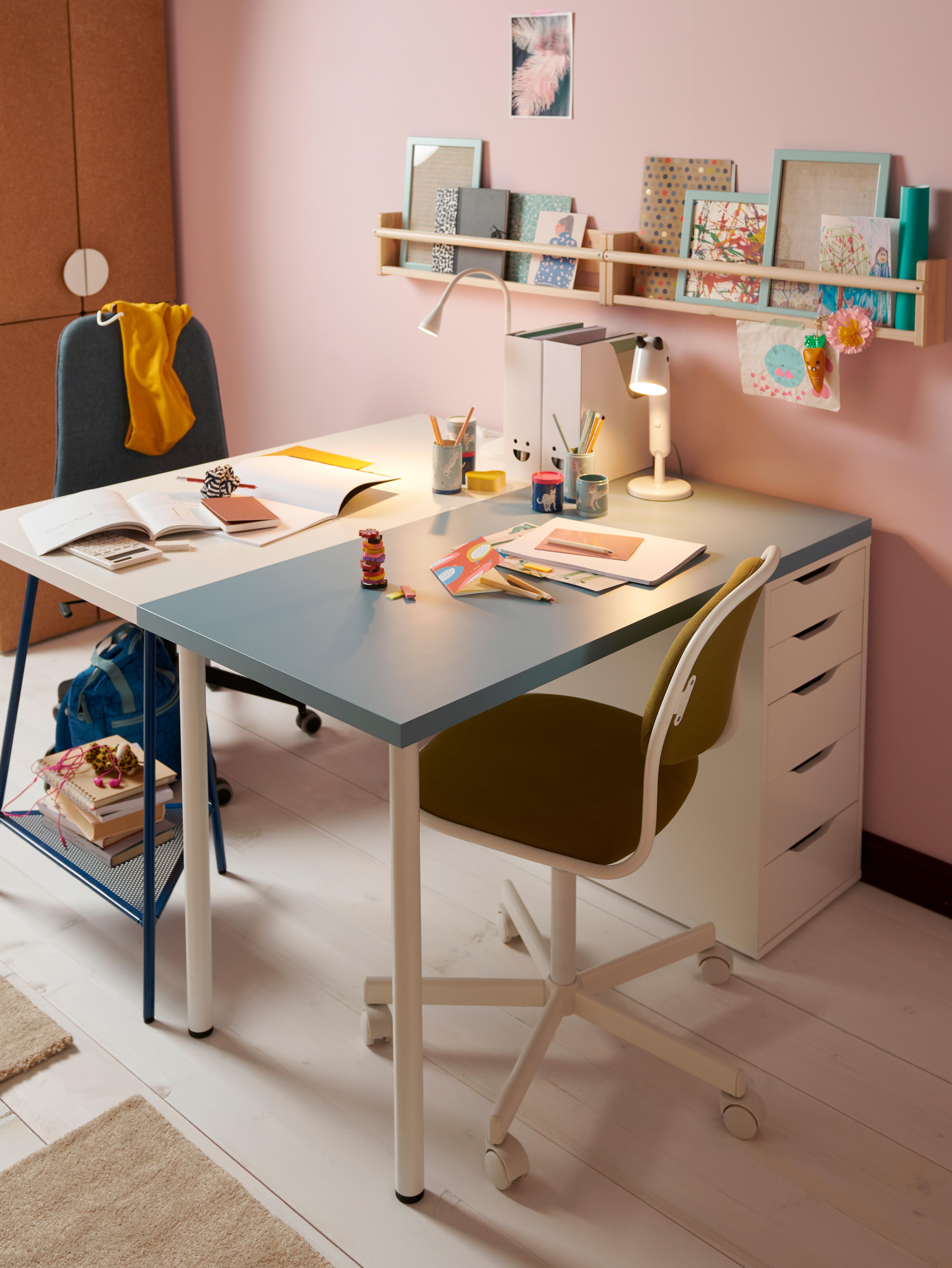 På et pastelfarvet børneværelse står to skriveborde med henholdsvis en hvid og en blå bordplade vendt mod hinanden med skrivebordsstole.