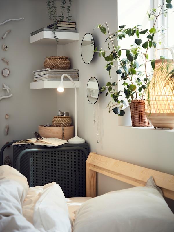 Une tête de lit en bois peu profonde, contre une fenêtre ornée d'une plante et d'une lampe. Une petite commode accueillant une liseuse et un carnet.