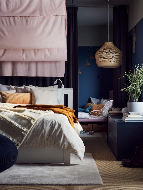 Produljivi krevet pored bijelog kreveta s posteljinom bijele i bež boje, tamnobež ukrasni jastuk, zavjese roza boje i visilica od bambusa.