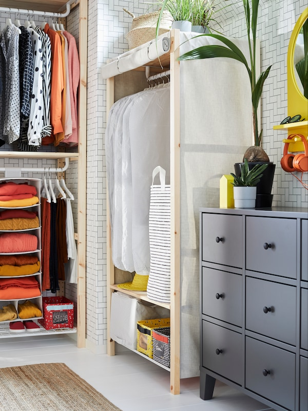 Open storage wardrobes made with IVAR pine shelving units with a beige pull-down textile cover and white clothes covers.