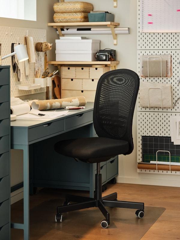 كرسي مكتب أسودوواقي أرضيةومكتب رمادي-فيروزي ولوحات تعليق بيضاء ولفات ورق.