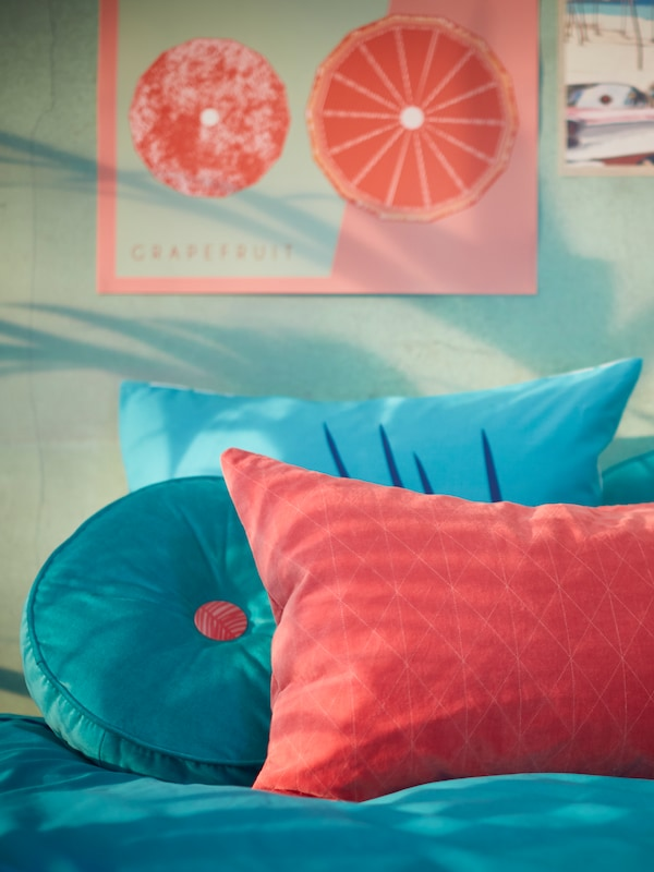 A turquoise GRACIÖS cushion and one in a pink GRACIÖS cushion cover lie on a bed under a wall decorated with posters.