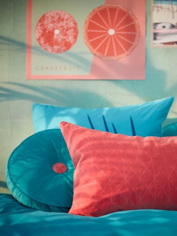 Une collection de housses de coussin, de coussins et de taies d'oreiller GRACIÖS dans des tons turquoise et roses, posés sur un lit.