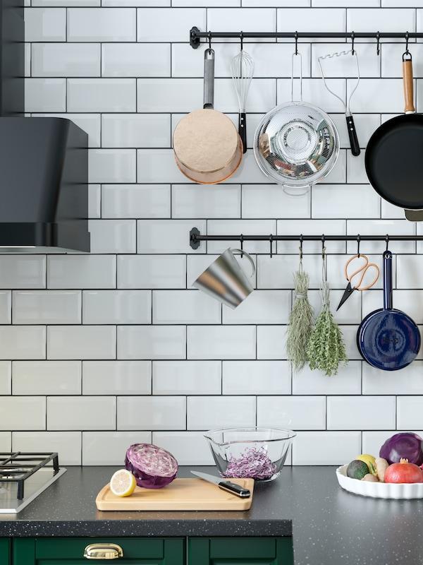 Due binari neri su una parete della cucina con piastrelle bianche sopra un piano di lavoro. Ai binari sono appesi utensili da cucina e spezie essiccate.
