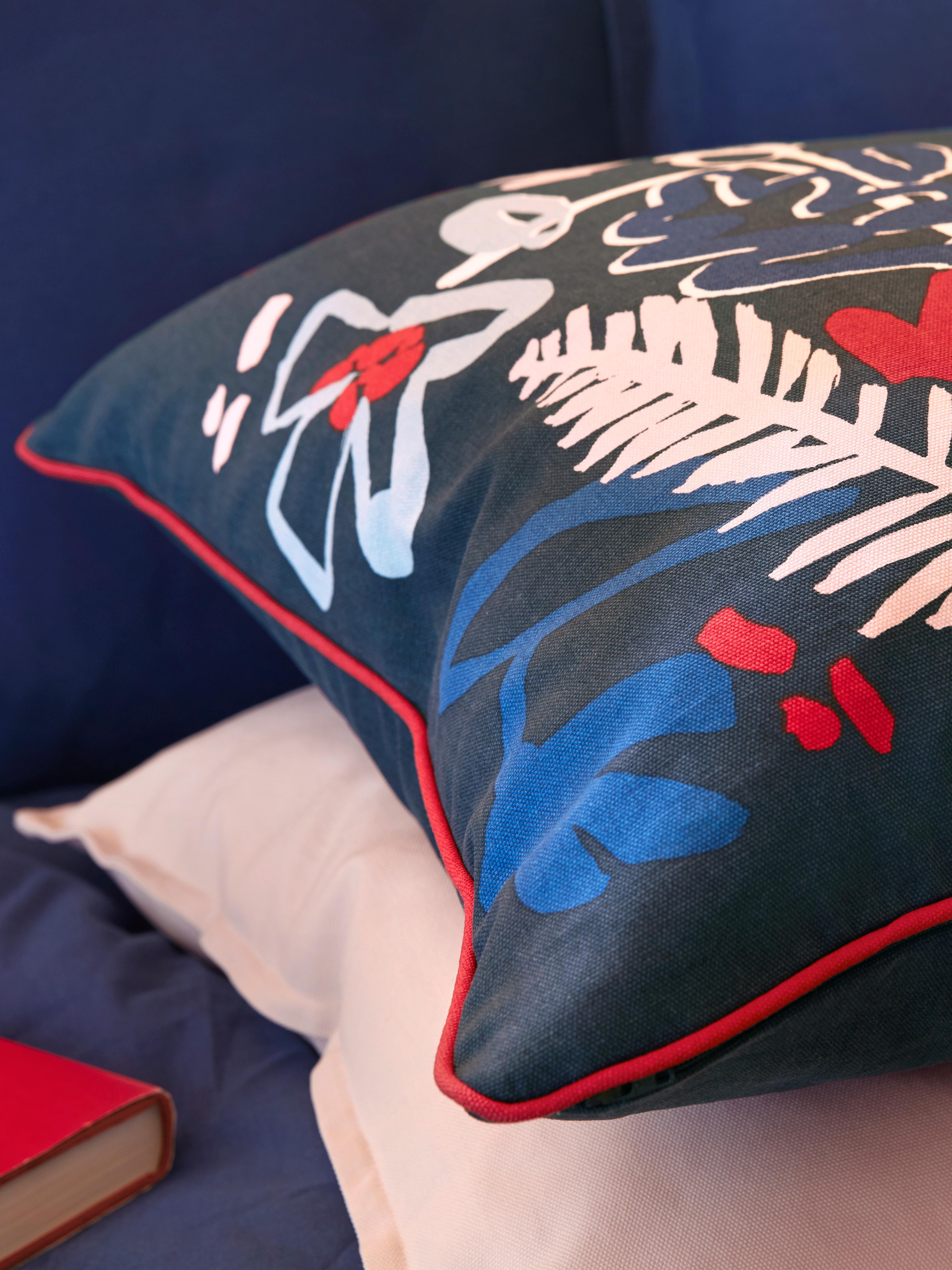Ukrasni jastuk s MÅLARBORSTE ukrasnom jastučnicom plave boje i više boja, na drugom rozom ukrasnom jastuku i pored knjige.