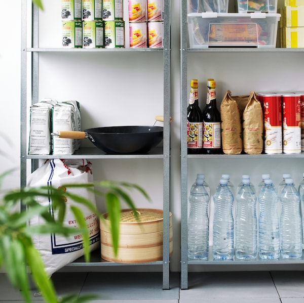 Two metal shelving units standing next to each other containing bottles of water, sauces, canned goods, and more.