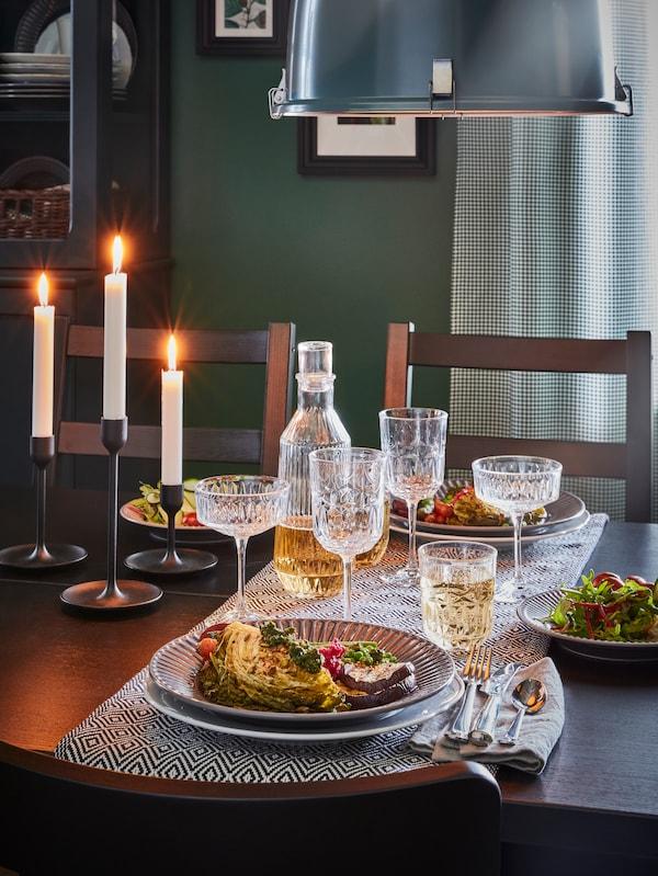 Une table noire éclairée par des bougies, un chemin de table noir et blanc, de la vaisselle pour un tête-à-tête et des verres au look vintage.