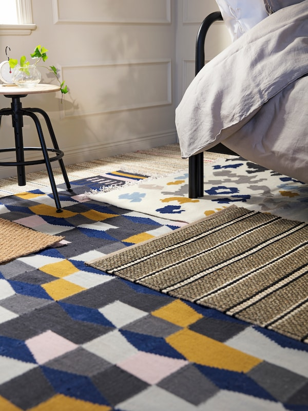 A bedroom corner with a lot of overlapping rugs with different patterns on the floor, and a stool and the end of a bed.